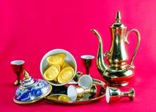 在红色背景的金锭金水罐茶玻璃benjarong 库存图片