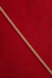在红色背景的金黄链子 免版税图库摄影