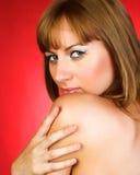 在红色背景的露胸部的女孩 图库摄影