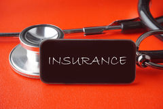在红色背景的黑听诊器 免版税库存照片