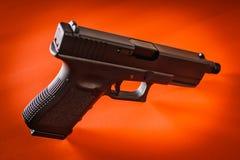 在红色背景的黑手枪 库存照片