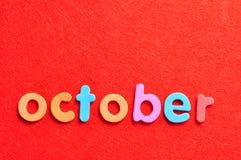 在红色背景的10月 免版税库存图片
