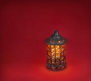 在红色背景的玻璃灯 免版税库存照片