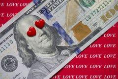 在红色背景的100美元充满题字爱 红心闭上他们的眼睛 金钱和贪婪概念爱  免版税图库摄影