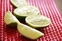 在红色背景的绿色柠檬 库存图片