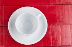 在红色背景隔绝的加奶咖啡杯子 库存照片