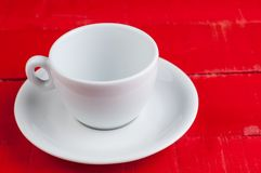 在红色背景隔绝的加奶咖啡杯子 免版税库存照片