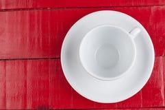 在红色背景隔绝的加奶咖啡杯子 库存图片