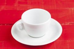 在红色背景隔绝的加奶咖啡杯子 免版税库存图片
