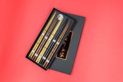 在红色背景隔绝的黑匣子的木筷子 免版税库存照片