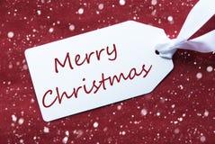 在红色背景,雪花,文本圣诞快乐的一个标签 免版税库存照片