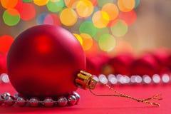 在红色背景水平的版本的大红色圣诞节球 库存照片