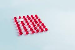 在红色胶囊栅格的一种白色圆的片剂  免版税图库摄影