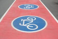 在红色自行车道路的自行车标志 免版税库存照片