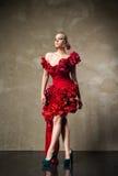 在红色花服的美好的白肤金发的模型 免版税库存照片