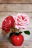 在红色花瓶的两朵玫瑰在年迈的木背景 免版税库存图片
