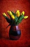 在红色花瓶的黄色郁金香在红色背景、春天或者复活节花,背景摄影为假日 免版税库存照片