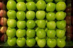 在红色苹果摊位之间的健康新绿色苹果摊位在超级市场 库存图片