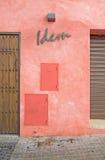 在红色草草做成的墙壁上的同前标志 库存照片