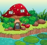 在红色蘑菇房子附近的一只蚂蚁 库存图片