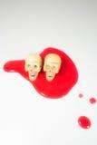 在红色血液万圣夜节日的两块头骨头 免版税库存照片