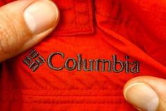 在红色衣裳的被绣的商标哥伦比亚在妇女手上 免版税库存照片