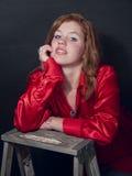 在红色衬衣微笑的红头发人 免版税库存图片