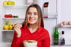 在红色衬衣穿戴的可爱的年轻女性模型,有有吸引力的神色,拿着碗用新鲜的沙拉,吃它高兴地巨大,有 免版税库存图片