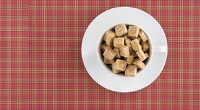 在红色被摆正的背景的加奶咖啡或茶杯充分的红糖立方体顶视图  饮食unhealty甜瘾 库存图片