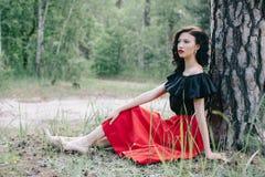 在红色裙子、黑夹克和红色嘴唇的年轻深色的模型 免版税库存图片