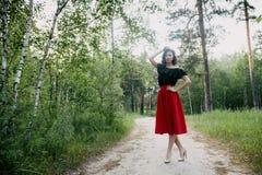 在红色裙子、黑夹克和红色嘴唇的年轻深色的模型 免版税库存照片