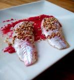 在红色调味汁的梭鱼 免版税图库摄影