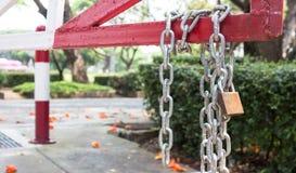 在红色路障碍的钢链发怒锁 免版税库存图片