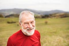 在红色运动衫的活跃资深赛跑者在自然休息 库存照片