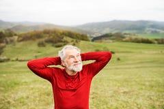 在红色运动衫的活跃资深赛跑者在自然休息 图库摄影