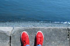 在红色运动鞋的腿在边缘站立 免版税图库摄影