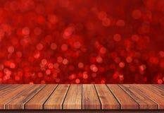 在红色迷离bokeh光背景的空的棕色木台式 库存照片