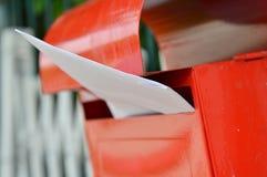 在红色邮箱的信件在家庭篱芭 图库摄影