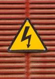 在红色金属墙壁背景的电危险广告标志 库存图片