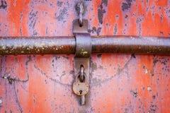 在红色金属门的老生锈的挂锁 库存照片