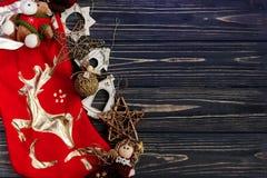 在红色长袜的圣诞节金黄时髦的玩具 装饰品边界 库存图片