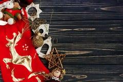 在红色长袜的圣诞节金黄时髦的玩具 装饰品边界 图库摄影