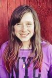 在红色门前面的女孩微笑的时尚运动衫 库存图片