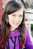 在红色门前面的女孩微笑的时尚运动衫 库存照片