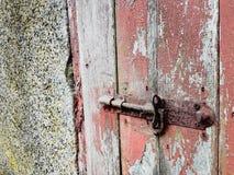 在红色门的生锈的门闩 图库摄影
