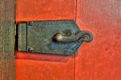 在红色门的老华丽金属锁 免版税库存照片