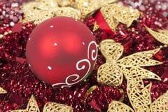 在红色闪亮金属片的圣诞节球喜欢背景 库存图片