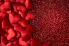 在红色闪烁纹理、华伦泰或者母亲节背景的一点红色缎心脏 免版税图库摄影