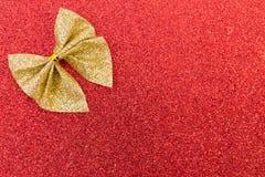 在红色闪烁背景的闪耀的金黄丝带 免版税库存图片