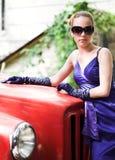 在红色附近的蓝色汽车女孩 免版税库存照片